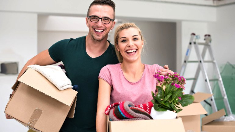 Happy couple holds packing boxes