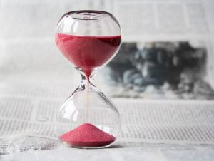 Hourglass with crimson sand showing how much time you can waste packing valuable items without help.