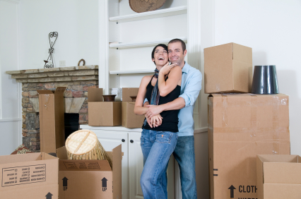 a couple standing in front of the moving boxes