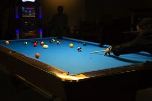 people play on the pool table while waiting for pool table movers to help them relocate their pool table