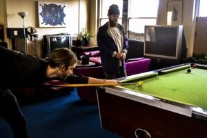 Two friends playing on the pool table in the living room after the pool table relocation