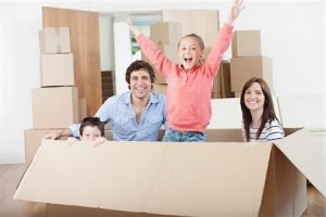 Parents with two children surrounded by boxes, smiling, satisfied with North Lauderdale Movers.