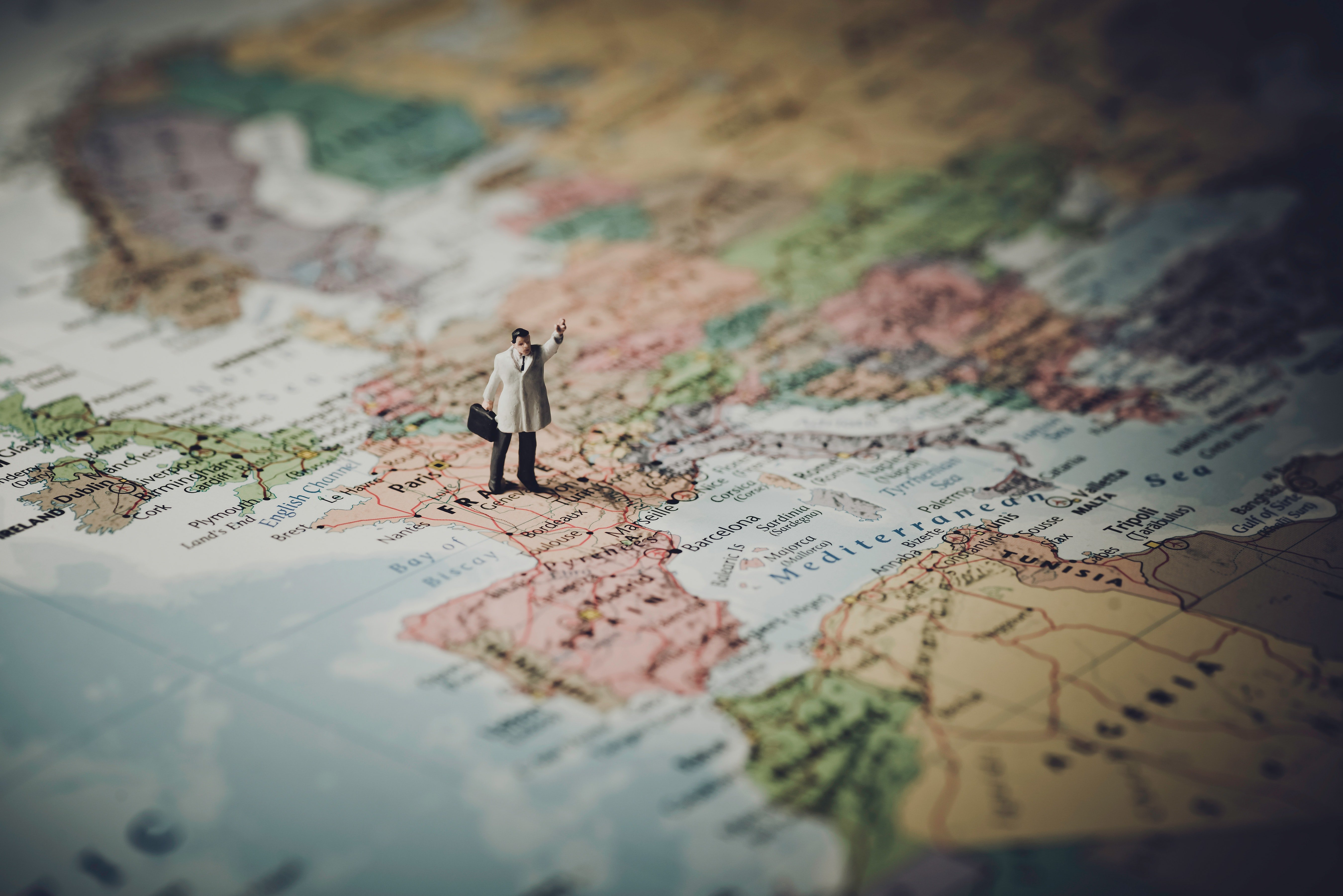 Miniature figure of a man standing on a map of Europe