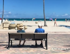 Elderly couple sitting on a wooden bench in front of a beach. Beaches are a large part of life here, and they are a good way to experience Miami like a local.