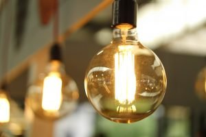 A close up of a light bulb. The rest of the photo is blurred, but we can see some more light bulbs in the background.