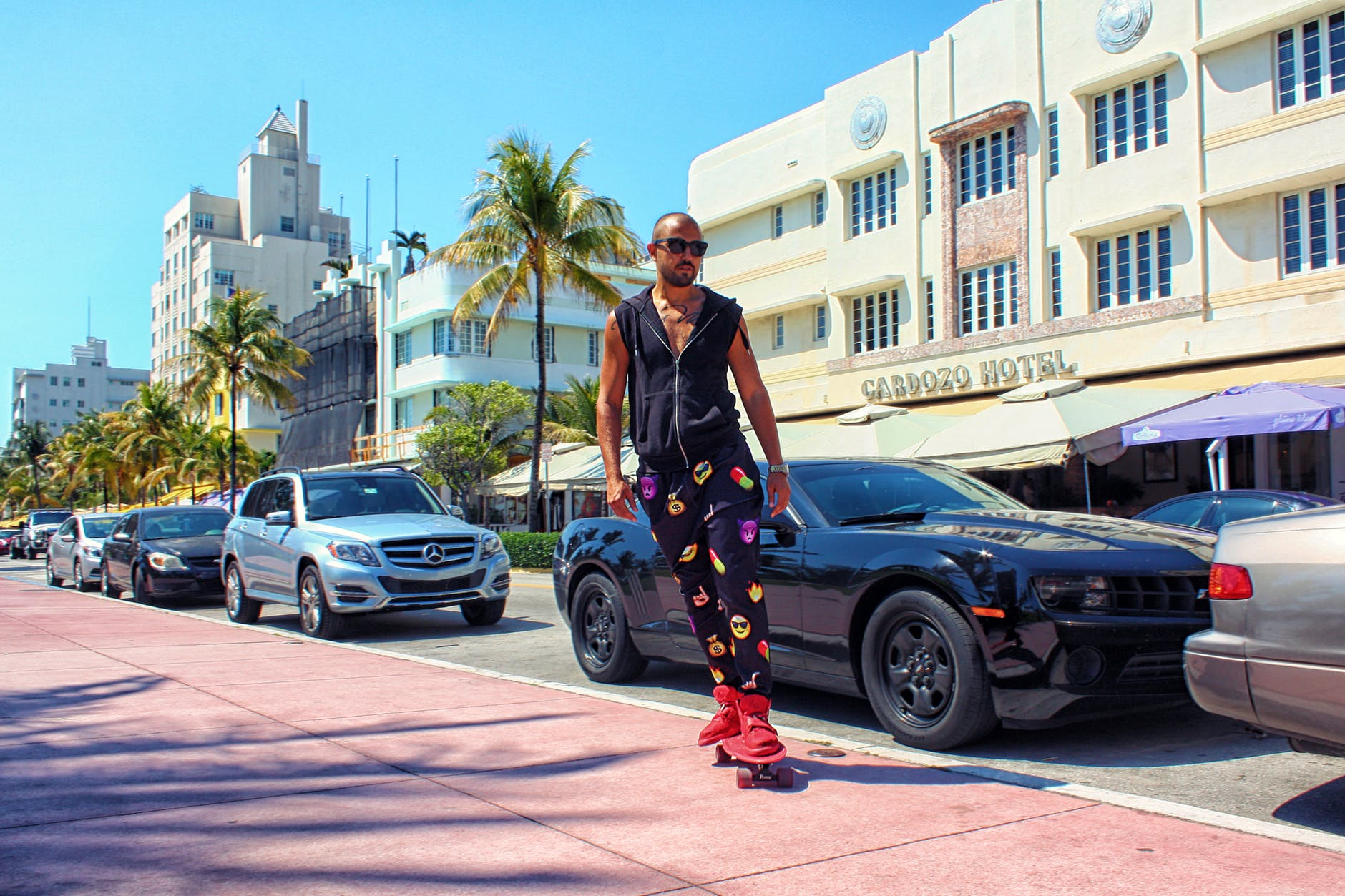 A man on the sidewalk in Miami. He is on a red skateboard. If you want to experience Miami like a local, you might need to make some adjustments to your lifestyle.
