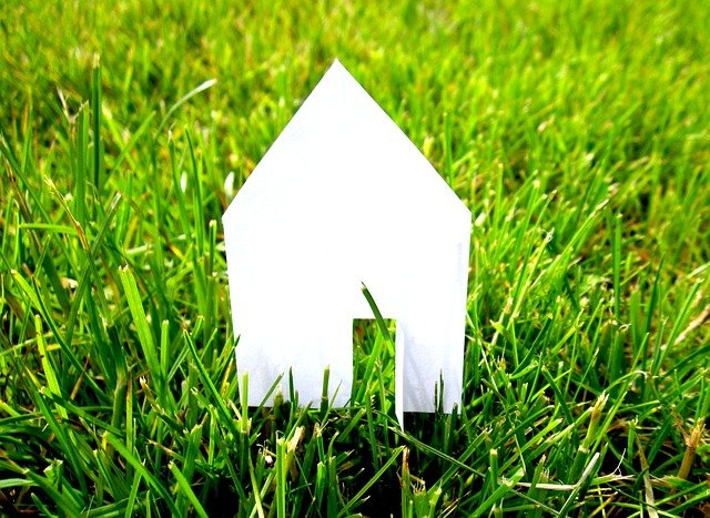 Cut-out shape of a house on a grass.