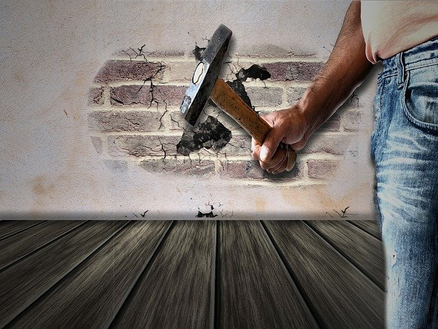 Remodeling contractors in Miami holding a hammer.
