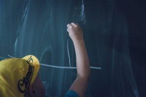 Boy in front of the blackboard
