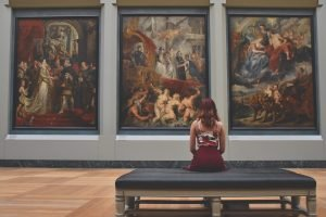 A woman sitting in front of artwork in one of the top museums in Miami to visit.
