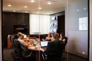 four people in a meeting - move your office to a bigger space