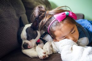 girl sleeping next to a dog - one of the best packing tips for busy mums