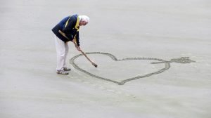 Old man drawing a heart in the sand