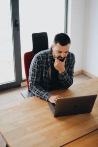 man thinking over laptop
