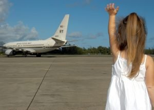Little girl waving goodbye to a plane. A con of relocating interstate with kids is having to leave people behind.