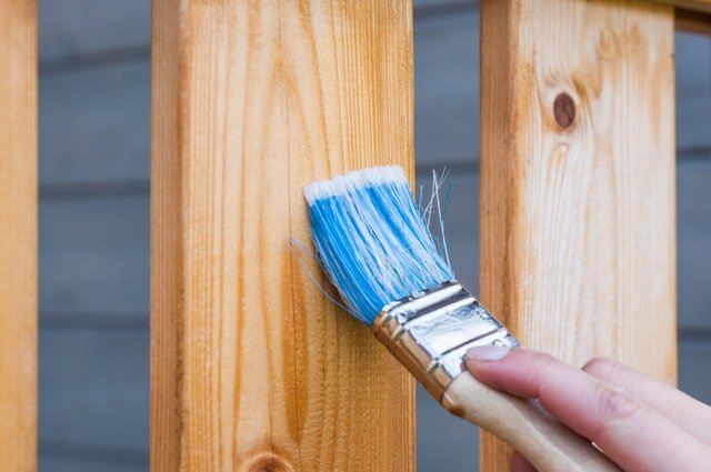 Painting a fence while doing a mobile home remodeling